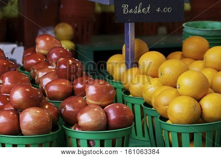 Small green baskets of apples and oranges at the outdoor/indoor Jean-Talon Market in Montreal, Quebec, on a bright day in September.
