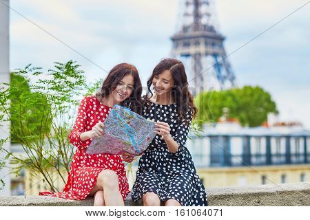 Beautiful Twin Sisters Using Map In Front Of Eiffel Tower