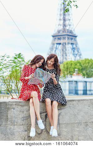 Beautiful Twin Sisters Using Map In Paris