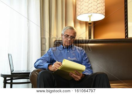 A senior businessman seated on the couch of his hotel room taking notes on a legal pad.