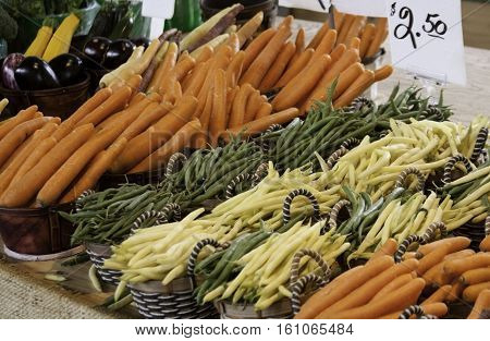 Rows of yellow and green beans and carrots on a display table at the outdoor/indoor Jean-Talon Market in Montreal, Quebec, on a bright day in September.