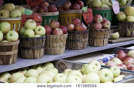 Large variety of red and yellow apples in wooden baskets along long shelving in front of an store at the outdoor/indoor Jean-Talon Market in Montreal, Quebec, on a bright day in September.