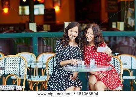 Beautiful Twin Sisters Drinking Coffee