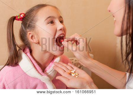 Hand puting tablet in a mouth to the little girl