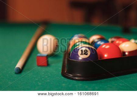 Billiard balls near by cue and chalk.