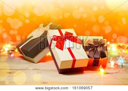 Three gift boxes and blinker on wooden background