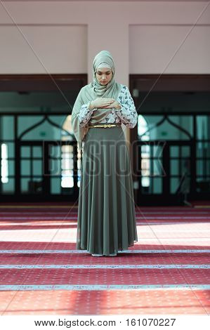 Young beautiful Muslim Woman Praying In Mosque.