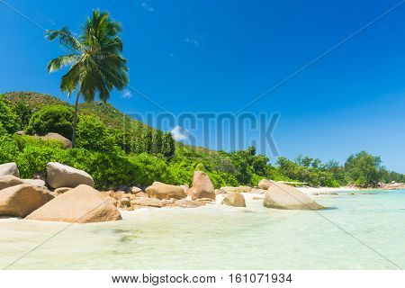 Beautiful beach Anse Takamaka seen from the granite boulders, La Digue island, Seychelles. Panorama