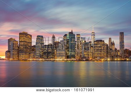 New York City - Famous Manhattan skylines at evening time, great illumination and moody clouds, NYC, USA