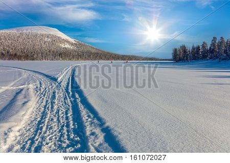 Skiing trail in beautiful winter area  and  skiing men, sunny weather - ski resort, Finland, Lapland