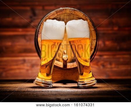 Two glasses of lager with old wooden keg