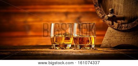 Two glasses of whiskey with ice cubes served on wooden planks with keg. Vintage countertop with highlight and a glass of hard liquor