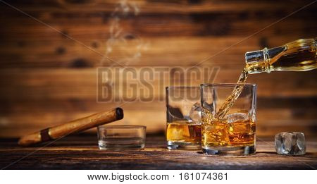 Pouring whiskey from bottle to two glasses with ice cubes, served on wooden planks. Vintage countertop with highlight and a glass of hard liquor