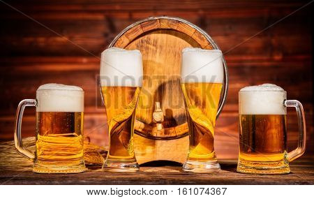 Various glasses of lager with old wooden keg