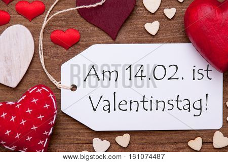 Label With German Text Am 14.2. Ist Valentinstag Means February 14th Is Valentines Day. Red Textile Hearts On Wooden Background. Flat Lay With Retro Or Vintage Style