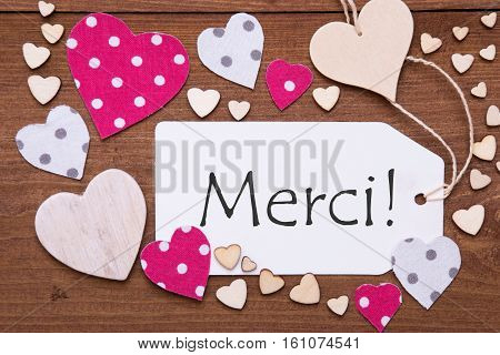 One Label With French Text Merci Means Thank You. Flat Lay View With Wooden Vintage Background. Pink Wooden And Paper Hearts.