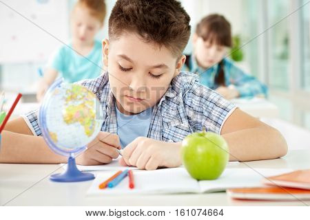 Diligent schoolboy sitting at lesson with over students