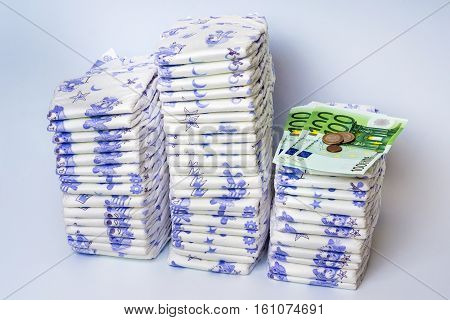 Pile Of Disposable Diapers With Euro Money