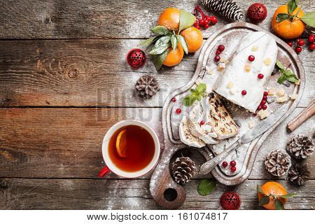 Christmas stollen, traditional German, European festive dessert cut into pieces on wooden background. Top view, Black background