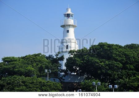 Xiao qingdao light house or lttle qingdao nestled among the trees against a blue sky in the city of Qingdao in Shandong province China.