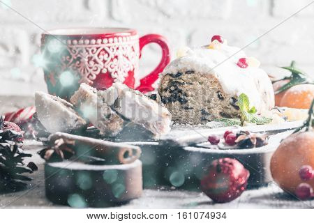 Christmas stollen, traditional German, European festive dessert cut into pieces on wooden background.