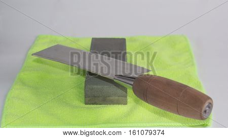 Knife sharpening caidao. Gray stone on a yellow background