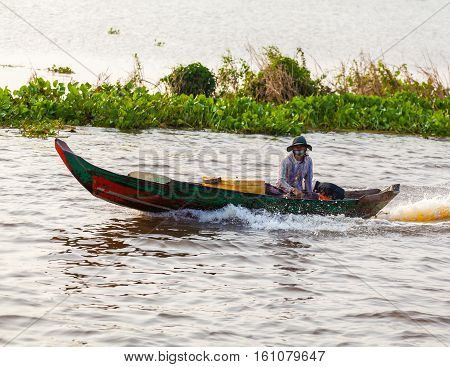 Tonle Sap Lake Siem Reap, Cambodia - OCTOBER 13, 2012: Asian woman floating on a motorboat. The life of the local residents
