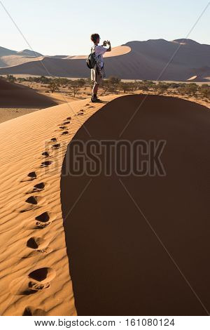 Tourist Holding Smart Phone And Taking Photo At Scenic Sand Dunes At Sossusvlei, Namib Desert, Namib