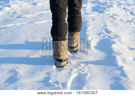 male legs in boots with galoshes are on the snow