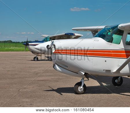 Light private planes parked on the airfield on a sunny summer day