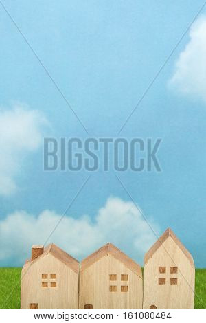 Houses on green grass over blue sky and clouds. Mortgage concept.