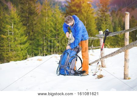 The Climber Pulls Things Out Of The Backpack.