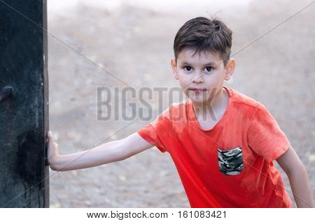 Boy with wet T-shirt. Playing with water. Water tap in the park.