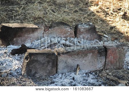 the cooled coals and ashes from the fire in a makeshift grill