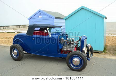 FELIXSTOWE, SUFFOLK, ENGLAND - AUGUST 27, 2016: Classic Blue Hot rod parked in front of beach huts  on seafront promenade.