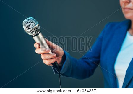 Elegant female journalist conducting business interview hand with microphone