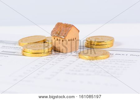 House and the stack of gold investment and real-estate concept