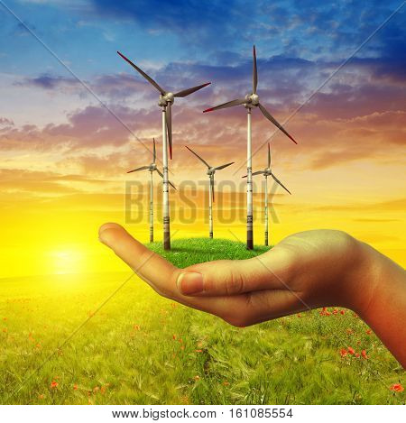 Wind turbines in hand at sunset. Clean energy concept.