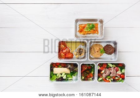 Healthy food delivery. Take away of natural organic fitness dishes for diet. Daily ratio nutrition pyramid meals in foil boxes on white wood. Top view, flat lay, copy space on wooden background