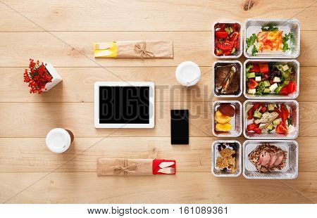 Healthy restaurant food mockup. Fresh daily meals delivery. Fitness nutrition for two, vegetable, meat and fruits in foil boxes, coffee, tablet and mobile. Top view, flat lay on wood with copy space