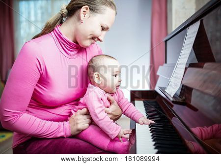 Happy Mother And Baby Daughter Are Playing Piano At Home