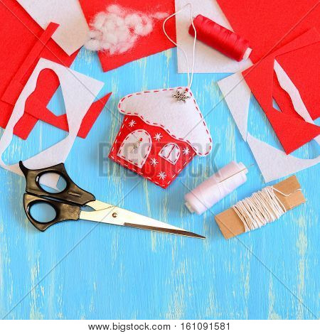 Christmas tree house decor sewn from red and white felt and decorated with snowflakes and metal elements. Tools and materials to create Christmas tree embellishment. Handmade DIY. Closeup. Top view poster