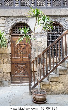 cairo, Egypt - December 10, 2016: View of the courtyard of Beit El Set Waseela (Waseela Hanem House) showing a wooden closed door and window with interleaved wooden grid and stair with wooden handrail leading to the upper floor Medieval Cairo Egypt
