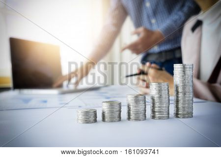 Person pointing while writing business plan at workplace with stacks of coins in graph chart. Saving and earning money concept.