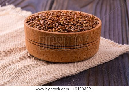 Brown flax seeds or flax seed in a small bowl on sacking