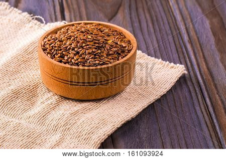 Brown flax seeds or linseeds in small bowl photographed overhead on dark wood