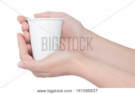 Hands holding white paper cup isolated on white background. Female hands with disposable cup over white background. Breakfast and coffee theme