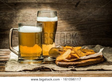 Beer in mug, glass on wooden table with and potato chips on board