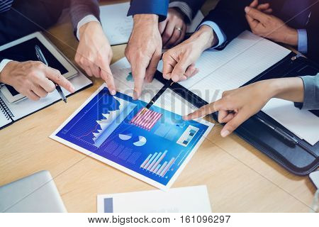 Cropped image of businesspeople discussing chart and graph in meeting at office