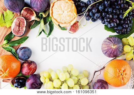 Fruit Background with Grape Plum Tangerines Figs on White Paper. Healthy Food Frame